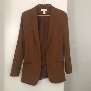 Brown tan blazer fitted over the hip